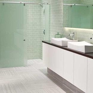 Inspiration pour une salle de bain principale minimaliste de taille moyenne avec un placard à porte plane, des portes de placard blanches, une douche d'angle, un WC à poser, un carrelage gris, un carrelage en pâte de verre, un mur gris, un sol en carrelage de porcelaine, une vasque, un plan de toilette en surface solide, un sol gris et une cabine de douche à porte coulissante.