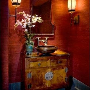 Foto de cuarto de baño con ducha, asiático, de tamaño medio, con armarios estilo shaker, puertas de armario de madera oscura, paredes rojas, lavabo sobreencimera, encimera de vidrio y suelo gris