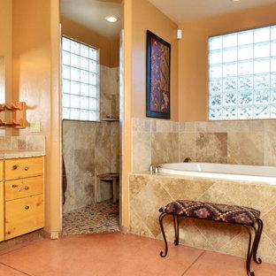 Неиссякаемый источник вдохновения для домашнего уюта: большая главная ванная комната с фасадами с утопленной филенкой, светлыми деревянными фасадами, накладной ванной, открытым душем, коричневой плиткой, плиткой из травертина, коричневыми стенами, бетонным полом, накладной раковиной, столешницей из плитки, оранжевым полом и открытым душем