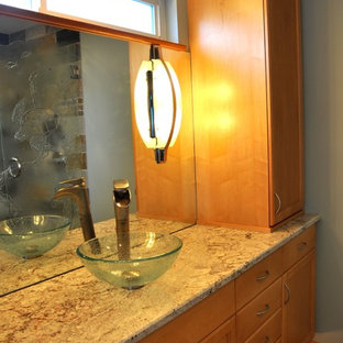 Inspiration for a small transitional stone tile slate floor corner shower remodel in Seattle with a vessel sink, recessed-panel cabinets, light wood cabinets, granite countertops and blue walls