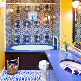 Photo of a medium sized mediterranean family bathroom in Minneapolis with a submerged sink, flat-panel cabinets, dark wood cabinets, engineered stone worktops, a submerged bath, a shower/bath combination, a one-piece toilet, blue tiles and yellow walls.