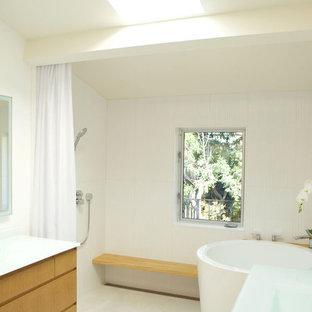 Новый формат декора квартиры: большая главная ванная комната в современном стиле с плоскими фасадами, светлыми деревянными фасадами, японской ванной, душем без бортиков, унитазом-моноблоком, белой плиткой, керамической плиткой, белыми стенами, полом из керамической плитки, монолитной раковиной, столешницей из переработанного стекла, белым полом, шторкой для душа и белой столешницей