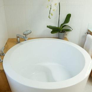 Foto på ett stort funkis vit en-suite badrum, med släta luckor, skåp i ljust trä, ett japanskt badkar, en kantlös dusch, en toalettstol med hel cisternkåpa, vit kakel, keramikplattor, vita väggar, klinkergolv i keramik, ett integrerad handfat, bänkskiva i återvunnet glas, vitt golv och dusch med duschdraperi