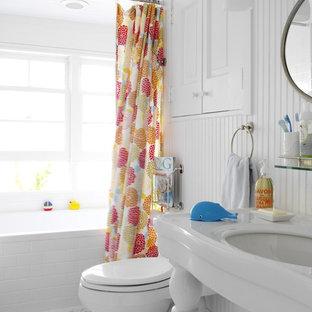 Inspiration pour une salle de bain marine de taille moyenne pour enfant avec un plan vasque, une baignoire en alcôve, un combiné douche/baignoire, un carrelage blanc, un carrelage métro, un placard avec porte à panneau surélevé, des portes de placard blanches, un WC séparé, un mur blanc, un sol en carrelage de porcelaine et un plan de toilette en surface solide.