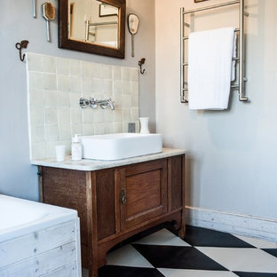 This is an example of a small romantic bathroom in London with recessed-panel cabinets, medium wood cabinets, a built-in bath, black and white tiles, white walls and a trough sink.
