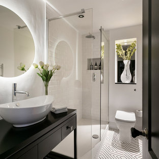 Inspiration for a small contemporary bathroom with flat-panel cabinets, black cabinets, a walk-in shower, a one-piece toilet, white tiles, metro tiles, white walls, a vessel sink, white floors, an open shower and black worktops.