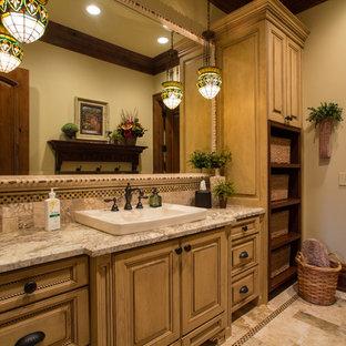 ソルトレイクシティの地中海スタイルのおしゃれな浴室 (オーバーカウンターシンク、レイズドパネル扉のキャビネット、ベージュのタイル、黄色いキャビネット) の写真