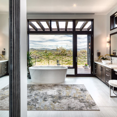 Mid-sized mountain style master gray floor freestanding bathtub photo in Phoenix with shaker cabinets, dark wood cabinets, gray walls, a vessel sink and white countertops