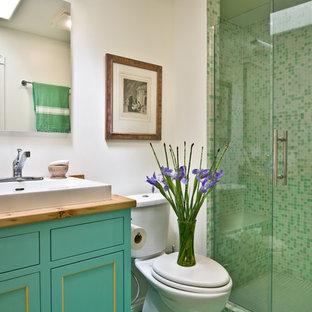 Пример оригинального дизайна: ванная комната среднего размера в стиле кантри с фасадами с декоративным кантом, бирюзовыми фасадами, душем в нише, раздельным унитазом, зеленой плиткой, керамогранитной плиткой, белыми стенами, полом из керамогранита, душевой кабиной, настольной раковиной, столешницей из дерева, зеленым полом и душем с распашными дверями