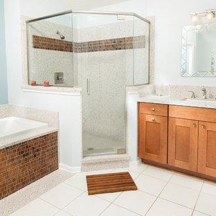 Diseño de cuarto de baño principal, tradicional renovado, de tamaño medio, con armarios estilo shaker, puertas de armario de madera oscura, bañera encastrada, ducha esquinera, baldosas y/o azulejos marrones, baldosas y/o azulejos naranja, paredes azules, lavabo bajoencimera, suelo blanco y ducha con puerta con bisagras