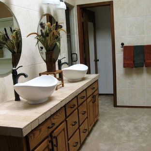 Example of an eclectic master beige tile and ceramic tile brown floor bathroom design in Albuquerque with raised-panel cabinets, dark wood cabinets, beige walls, a vessel sink and tile countertops