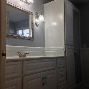 Ispirazione per una stanza da bagno padronale tradizionale di medie dimensioni con ante con bugna sagomata, ante bianche, doccia alcova, WC a due pezzi, piastrelle blu, pareti grigie, pavimento in vinile, lavabo integrato, top in marmo, pavimento grigio, porta doccia scorrevole e top bianco