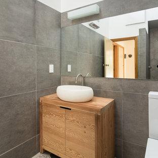 Ispirazione per una piccola stanza da bagno padronale minimalista con consolle stile comò, ante in legno scuro, doccia aperta, WC monopezzo, piastrelle grigie, piastrelle in ceramica, pareti grigie, lavabo rettangolare e top in legno