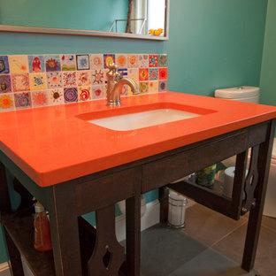 Modelo de cuarto de baño ecléctico, de tamaño medio, con lavabo bajoencimera, puertas de armario de madera en tonos medios, encimera de cuarzo compacto, sanitario de dos piezas, baldosas y/o azulejos de cerámica, paredes verdes, suelo de baldosas de porcelana y encimeras naranjas