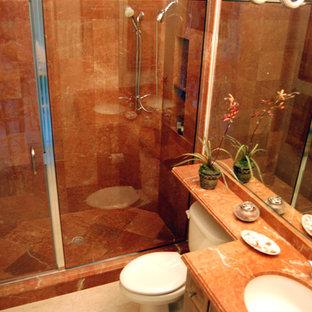 タンパの小さいトラディショナルスタイルのおしゃれなバスルーム (浴槽なし) (アンダーカウンター洗面器、レイズドパネル扉のキャビネット、中間色木目調キャビネット、アルコーブ型シャワー、一体型トイレ、ピンクのタイル、オレンジの壁、トラバーチンの床、大理石の洗面台、ベージュの床、開き戸のシャワー、大理石タイル) の写真