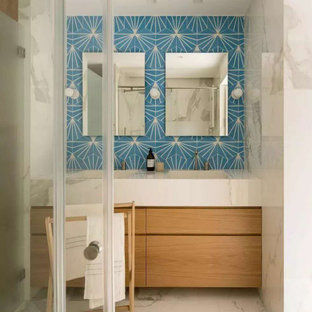 Mid-sized beach style bathroom in Other with flat-panel cabinets, light wood cabinets, a freestanding tub, an open shower, blue tile, porcelain tile, with a sauna, tile benchtops, a hinged shower door, white benchtops, a double vanity, a built-in vanity, white walls, cement tiles, an undermount sink, white floor and brick walls.