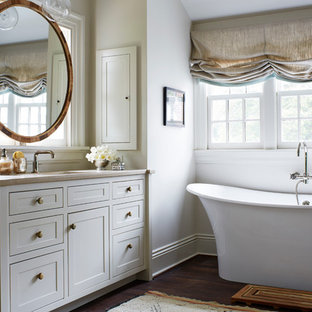 Cette photo montre une salle de bain nature avec un placard à porte shaker, des portes de placard grises, une baignoire indépendante, un mur blanc, un lavabo encastré et un sol en bois foncé.