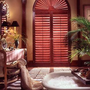 Large beach style master medium tone wood floor claw-foot bathtub photo in Denver with orange walls