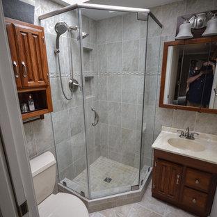 Ispirazione per una piccola stanza da bagno padronale american style con lavabo integrato, ante con bugna sagomata, ante in legno scuro, top in superficie solida, doccia ad angolo e WC monopezzo