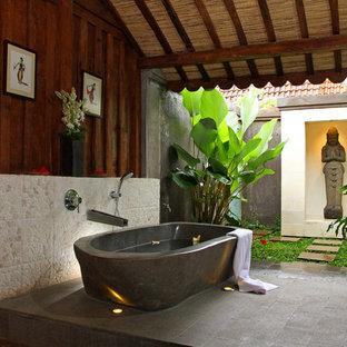 Immagine di una stanza da bagno tropicale con vasca freestanding e piastrelle di ciottoli