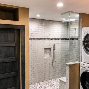 デンバーの中サイズのインダストリアルスタイルのおしゃれなバスルーム (浴槽なし) (フラットパネル扉のキャビネット、濃色木目調キャビネット、段差なし、一体型トイレ、白いタイル、セラミックタイル、黄色い壁、コンクリートの床、一体型シンク、人工大理石カウンター、グレーの床、オープンシャワー、ベージュのカウンター) の写真