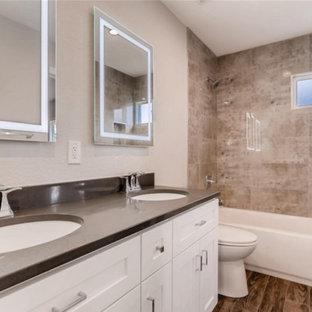 Foto di una stanza da bagno con doccia design con ante in stile shaker, ante bianche, vasca ad alcova, vasca/doccia, piastrelle rosa, piastrelle di marmo, pareti beige, lavabo sottopiano, pavimento grigio e top marrone