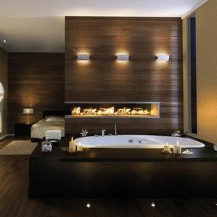 Immagine di una stanza da bagno design con vasca idromassaggio, piastrelle marroni e piastrelle effetto legno