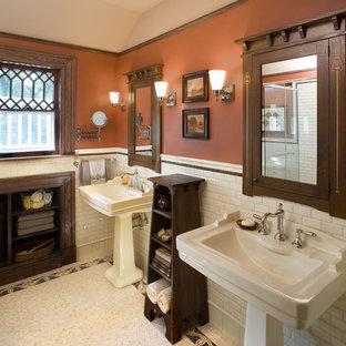 Immagine di una stanza da bagno stile americano con lavabo a colonna e pareti arancioni