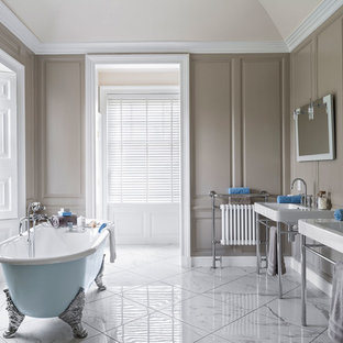 Large elegant master white tile marble floor claw-foot bathtub photo in Berkshire with brown walls, a console sink and open cabinets