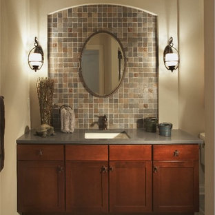 Inspiration for a medium sized mediterranean bathroom in Milwaukee with shaker cabinets, medium wood cabinets, a two-piece toilet, beige tiles, brown tiles, grey tiles, multi-coloured tiles, stone tiles, beige walls, slate flooring, a submerged sink and solid surface worktops.