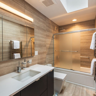Photo of a contemporary 3/4 bathroom in Other with flat-panel cabinets, blue cabinets, an alcove tub, a shower/bathtub combo, brown tile, light hardwood floors, an undermount sink, brown floor, a sliding shower screen and white benchtops.