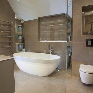 Foto på ett stort funkis en-suite badrum, med ett konsol handfat, ett fristående badkar, en dusch i en alkov, en vägghängd toalettstol, beige kakel, porslinskakel, klinkergolv i porslin, släta luckor, bruna väggar och bänkskiva i glas