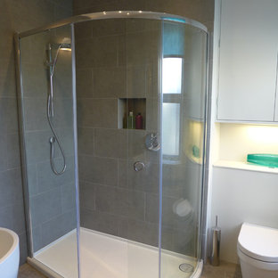 Photo of a medium sized contemporary family bathroom in Other with flat-panel cabinets, grey cabinets, wooden worktops, a corner shower, a wall mounted toilet, grey tiles, porcelain tiles, grey walls and lino flooring.