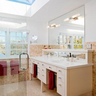 Modelo de cuarto de baño principal, contemporáneo, de tamaño medio, con armarios tipo mueble, puertas de armario beige, ducha esquinera, baldosas y/o azulejos beige, baldosas y/o azulejos de cerámica, paredes blancas, suelo de corcho, lavabo integrado, encimera de cemento, suelo beige y ducha con puerta con bisagras