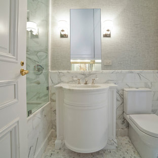 Inspiration for a mid-sized traditional master bathroom in New York with raised-panel cabinets, an alcove shower, a bidet, white tile, metal tile, grey walls, vinyl floors, an undermount sink, marble benchtops, grey floor, a hinged shower door and white benchtops.
