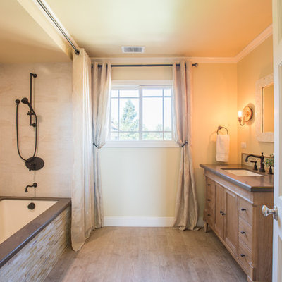 Inspiration for a large timeless beige tile and porcelain tile porcelain tile tub/shower combo remodel in San Francisco with an undermount sink, recessed-panel cabinets, quartz countertops, an undermount tub and yellow walls