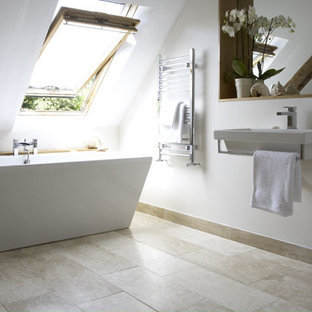 Design ideas for a small contemporary ensuite bathroom in Sydney with a wall-mounted sink, wooden worktops, a freestanding bath, a walk-in shower, a wall mounted toilet, beige tiles, stone tiles, beige walls and limestone flooring.