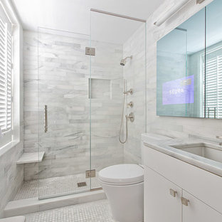 Inspiration for a small contemporary master white tile and stone tile marble floor bathroom remodel in New York with an undermount sink, white cabinets, marble countertops and flat-panel cabinets