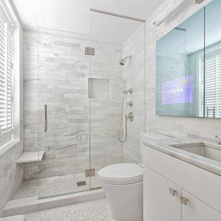 Modern inredning av ett litet en-suite badrum, med ett undermonterad handfat, vita skåp, marmorbänkskiva, vit kakel, stenkakel, marmorgolv och släta luckor