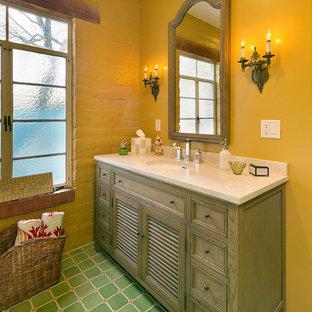 Idee per una stanza da bagno tradizionale con lavabo sottopiano, ante a persiana, ante in legno scuro, pareti gialle e pavimento verde