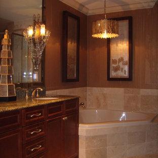 Ispirazione per una stanza da bagno padronale classica di medie dimensioni con ante con bugna sagomata, ante rosse, vasca ad angolo, piastrelle beige, piastrelle in travertino, pareti marroni, pavimento in travertino, lavabo sottopiano, top in granito, pavimento beige e top marrone