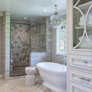 Immagine di una stanza da bagno classica con ante con riquadro incassato, ante bianche, vasca freestanding, piastrelle grigie e pareti grigie