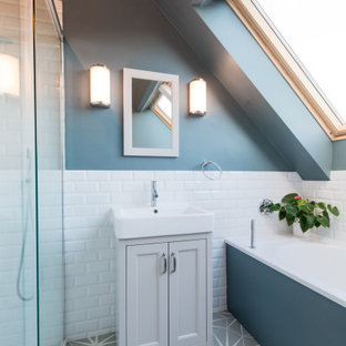 Inspiration for a classic bathroom in London with recessed-panel cabinets, grey cabinets, an alcove bath, an alcove shower, white tiles, metro tiles, blue walls, a console sink and grey floors.