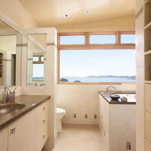 Modelo de cuarto de baño contemporáneo con lavabo integrado, armarios con paneles lisos, puertas de armario beige, baldosas y/o azulejos beige, bañera japonesa y encimeras marrones