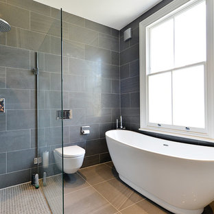 Inspiration for a medium sized modern family bathroom in London with flat-panel cabinets, dark wood cabinets, a freestanding bath, a walk-in shower, a one-piece toilet, black tiles, ceramic tiles, black walls, ceramic flooring, a built-in sink, tiled worktops, black floors and an open shower.