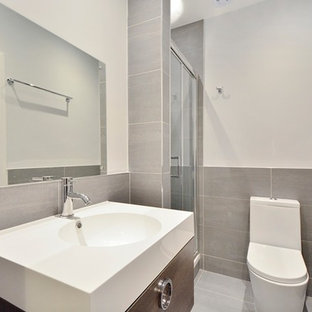 This is an example of a medium sized modern family bathroom in London with flat-panel cabinets, dark wood cabinets, a freestanding bath, a walk-in shower, a one-piece toilet, black tiles, ceramic tiles, black walls, ceramic flooring, a built-in sink, tiled worktops, black floors and an open shower.