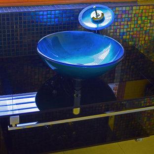 Foto de cuarto de baño con ducha, moderno, pequeño, con lavabo sobreencimera, encimera de vidrio, baldosas y/o azulejos multicolor, baldosas y/o azulejos de vidrio y paredes amarillas