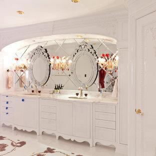 Ispirazione per un'ampia stanza da bagno padronale vittoriana con ante con bugna sagomata, ante bianche, piastrelle grigie, piastrelle a specchio, pareti bianche, pavimento con piastrelle a mosaico, lavabo sottopiano, top in marmo, pavimento multicolore e top bianco