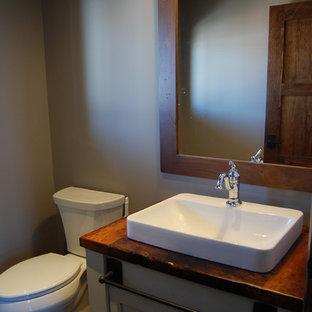 Пример оригинального дизайна: маленькая ванная комната в стиле рустика с фасадами с утопленной филенкой, белыми фасадами, столешницей из дерева и коричневой столешницей