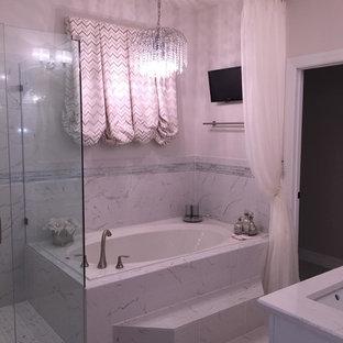 Exemple d'une douche en alcôve principale tendance de taille moyenne avec un placard avec porte à panneau encastré, des portes de placard blanches, une baignoire posée, un WC à poser, un mur blanc, un sol en marbre, un lavabo encastré et un plan de toilette en marbre.